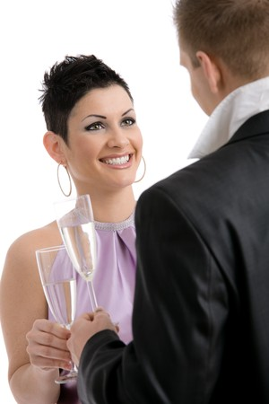 Trendy young couple clinking with champagne. Isolated on white background, selective focus on woman. photo
