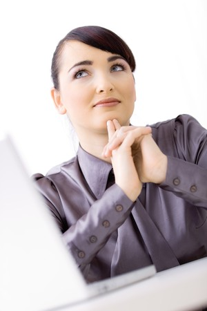 undoubting: Young attractive businesswoman sitting at desk at office, thinking. Stock Photo