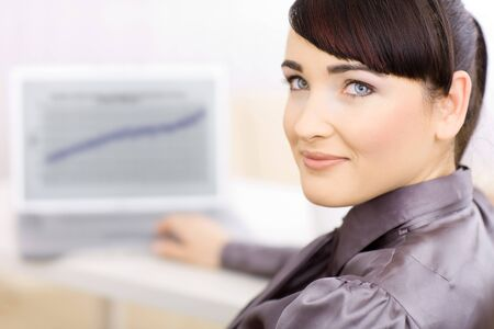 undoubting: Happy smiling businesswoman working at her desk and looking at camera. Stock Photo