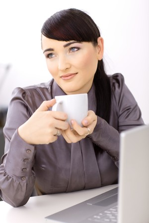 EASE: Young businesswoman daydreaming over her coffe in the office. Stock Photo