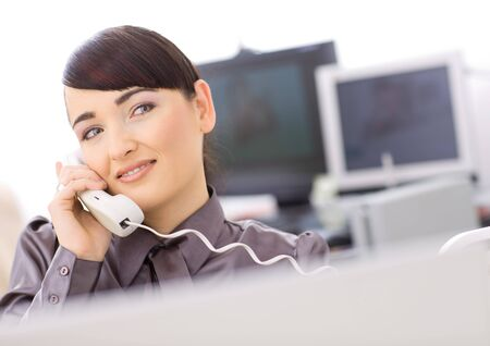 Young female customer service operator talking on landline phone, smiling. photo
