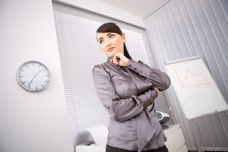 undoubting: Young businesswoman thinking in office preparing for her presentation beside a whiteboard. Stock Photo