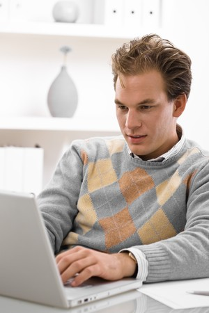 sinecure: Young man working on laptop computer at home. Stock Photo