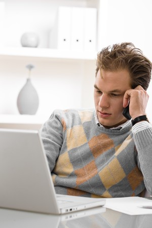 sinecure: Young man using laptop and calling on phone at home. Stock Photo
