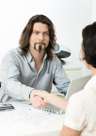 Businessman shaking hands with applicant during job interview in office. photo