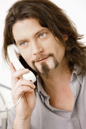 Closeup portrait of bearded man talking on landline phone. Stock Photo - 4366517