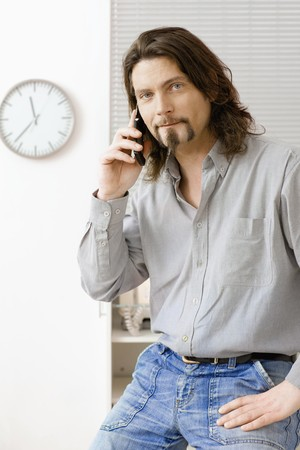 busy beard: Casual office worker talking on mobile phone in office. Stock Photo