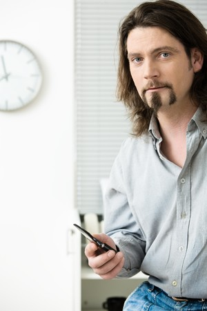 mobilephones: Casual office worker using mobile phone in office, writing text meaasage.
