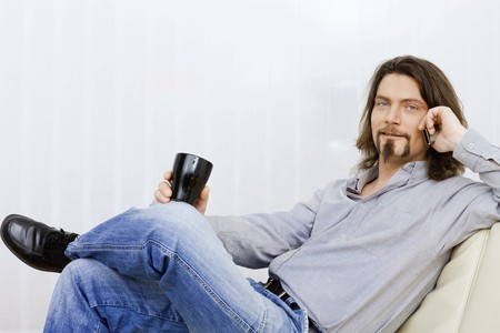 busy beard: Relaxed man talking on mobile phone, sitting on a couch and holding a coffee cup in hand.