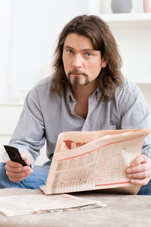 Man using mobile phone and holding newspaper in hand, sitting in living room at home. Stock Photo - 4366498