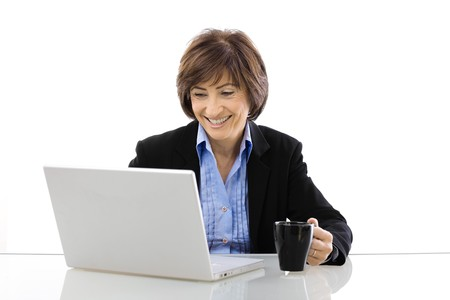 Senior businesswoman using laptop computer sitting at desk, looking at screen and smiling. Isolated on white background. photo