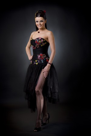 Beautiful young woman wearing a black cocktail dress standing in sexy pose, smiling and looking at camera. photo