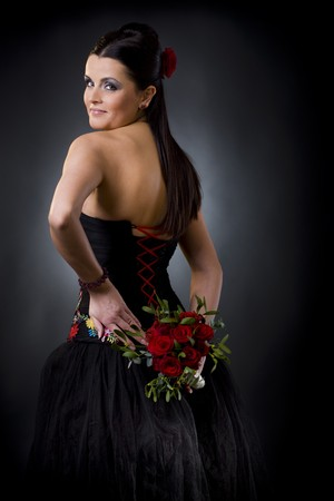 Beautiful young woman posing in a black cocktail dress holding a bouqet of red roses, looking back flirtatious. Stock Photo - 4387004