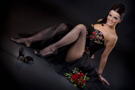 Beautiful young woman wearing a black cocktail dress sitting in sexy pose, smiling and looking at camera. photo
