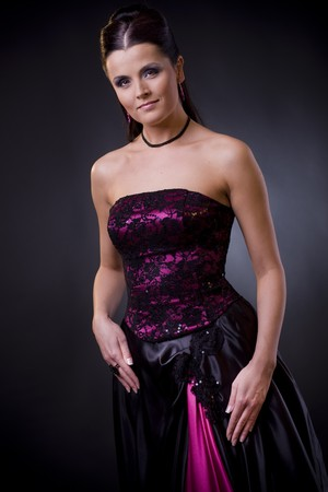 Studio portrait of a beautiful young woman wearing cocktail dress, smiling and looking in camera. photo