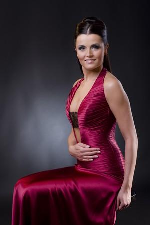 EVENING DRESS: Atractivo joven mujer sentada en una silla baja usando corte vestido de noche.