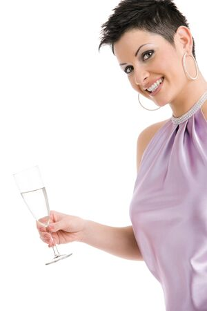 Happy young woman dressed for party holding a glass of champagne, smiling. Isolated on white background. photo