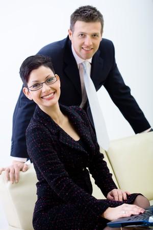 Happy business people sitting on sofa, smiling, isolated on white background. photo