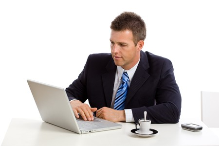 open collar: Businessman working on laptop computer, sitting at desk and looking seriously at screen.