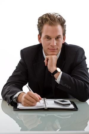 businesswear: Smiling businessman working at desk, white background.