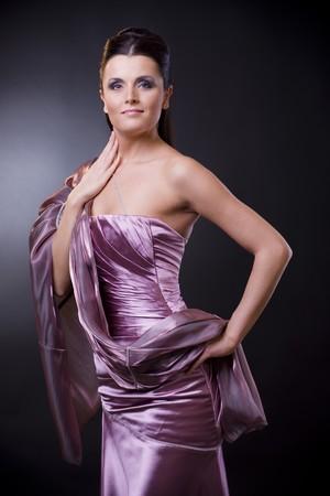 estola: Estudio de retrato de una joven mujer llevando un vestido de noche la luz violeta con robaron. Foto de archivo