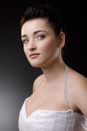 Portrait of a beautiful young bride wearing white wedding dress. photo