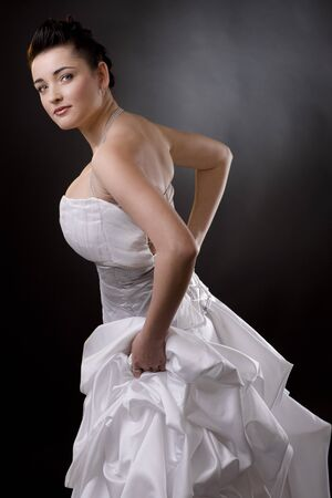 Portrait of a bride posing in a white wedding dress, holding her skirt and looking at camera. photo