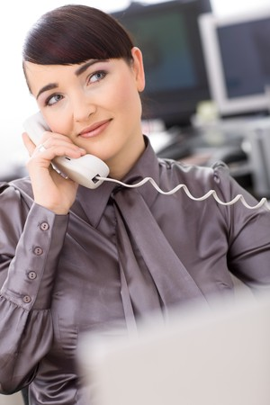 Young female customer service operator talking on landline phone, smiling. Stock Photo - 4387006