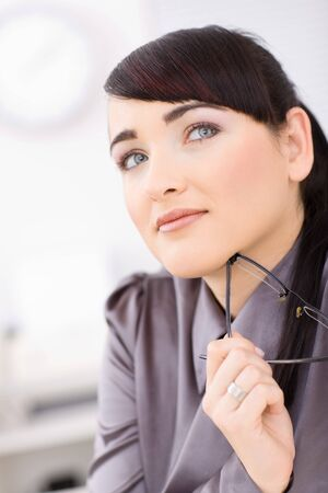 Pretty young businesswomen daydreaming at her desk, smiling, holding her glasses and looking up. photo