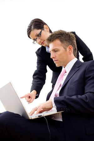 Businesspeople working together, using laptop computer, isolated on white background. photo