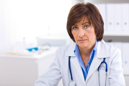 image consultant: Portrait of senior female doctor working at office.