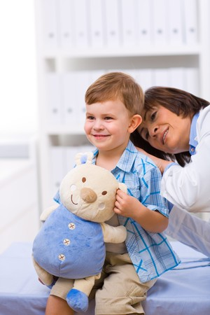 Senior female doctor examining happy child, smiling. photo