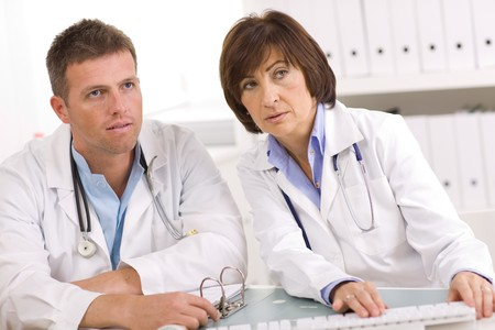 Medical team of male and female doctors sitting at desk. photo