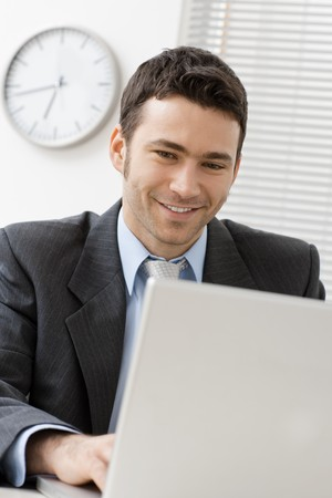 Happy young businessman working on laptop computer at office, smiling. Stock Photo - 4403092
