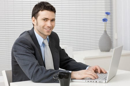 employee satisfaction: Happy young businessman working on laptop computer at office, smiling. Stock Photo