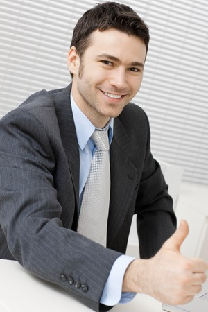 Happy young businessman showing success with thumb up at office, smiling. Stock Photo - 4403140