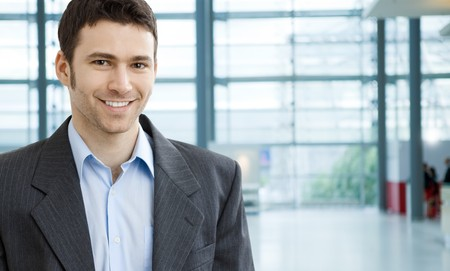 gratified: Portrait of successful young businessman at corporate location. Stock Photo
