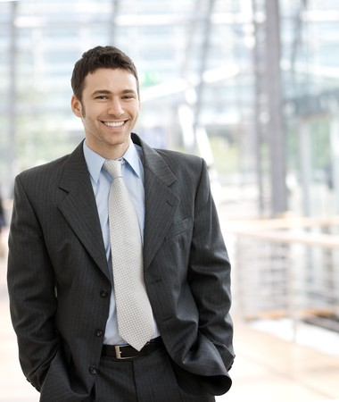 only young adults: Portrait of a happy young businessman, smiling, indoor.