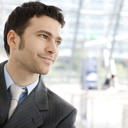 Portrait of a happy young businessman, smiling, indoor. photo