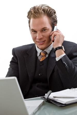 Businessman using laptop computer, mobile phone, white background photo