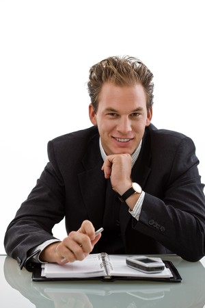 Smiling businessman working at desk, white background. photo