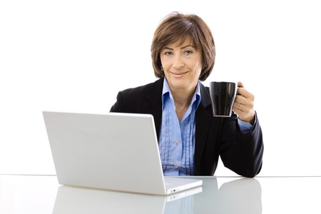 Senior businesswoman using laptop computer while drinking coffee, looking at camera and smiling. Isolated on white background. photo