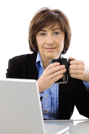 Senior businesswoman drinking coffee, isolated on white background. photo
