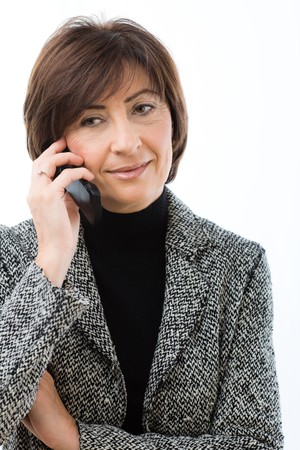 mature women only: Closeup portrait of senior businesswoman talking on mobile phone. Isolated on white background.