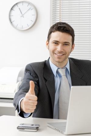 Happy jonge zakenman blijkt succes met duim op kantoor, lachend.