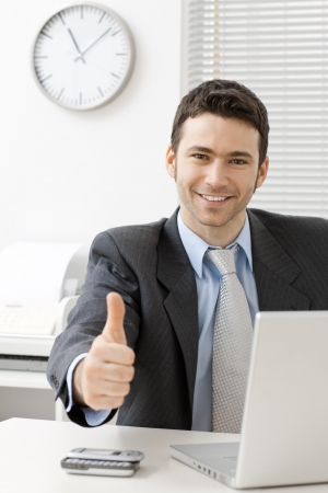 satisfied: Happy young businessman showing success with thumb up at office, smiling. Stock Photo