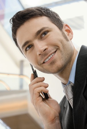 officetower: Young happy businessman calling on mobile phone, outdoor, smiling.