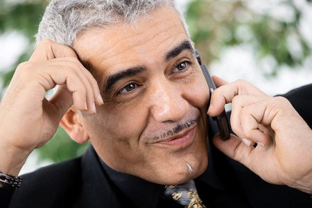 Gray haired mature businessman calling on mobile phone, smiling. photo