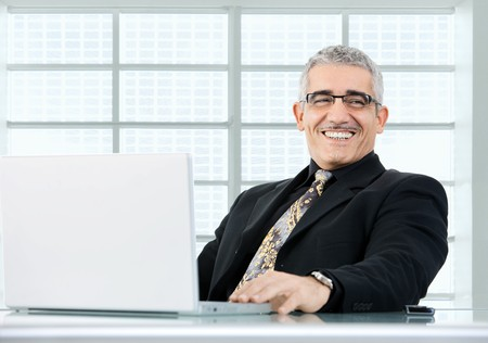 Happy mature businessman working on laptop computer at desk az office, smiling. photo