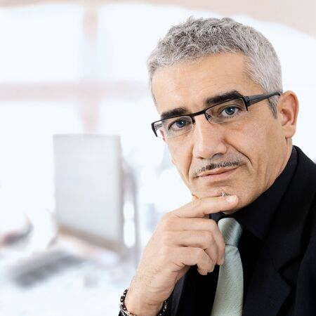 undoubting: Mature gray haired creative looking businessman thinking. Stock Photo